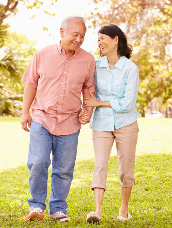 retired couple walking through park